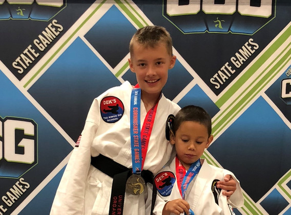 Jaylee and Anthony stand on the podium in appreciation of their gold medals.