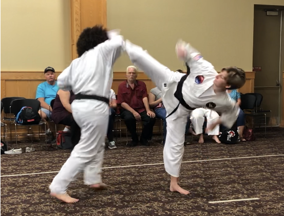 Anya throws a wheel kick to the head.  Keep your hands up!