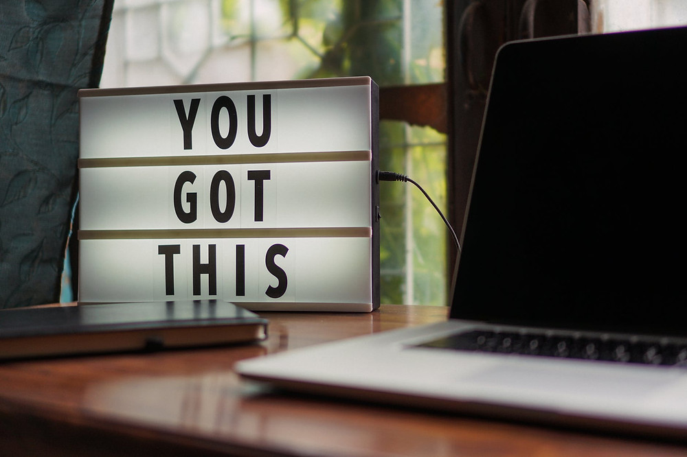 "A sign next to a laptop reads ""You got this"""