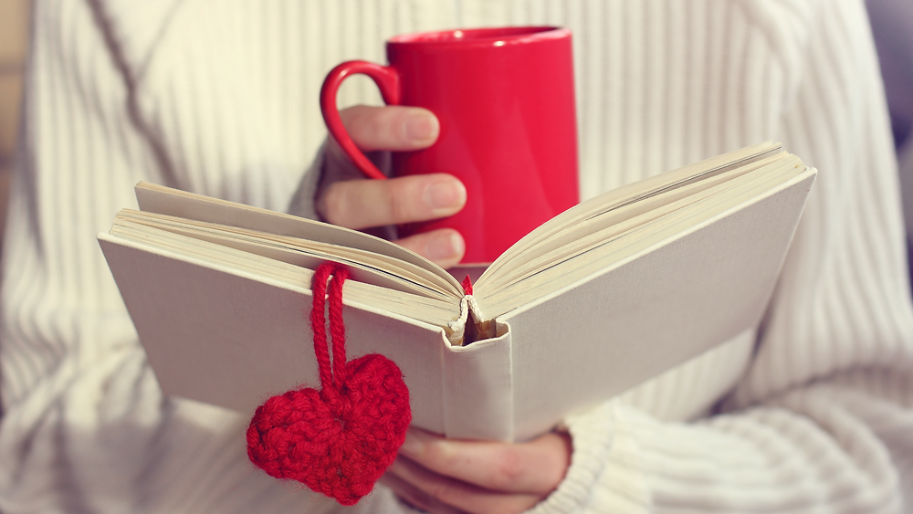Person holding a red coffee cup over an open book with a heart-shaped bookmark