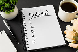 To do list. Notebook and coffee cup on b