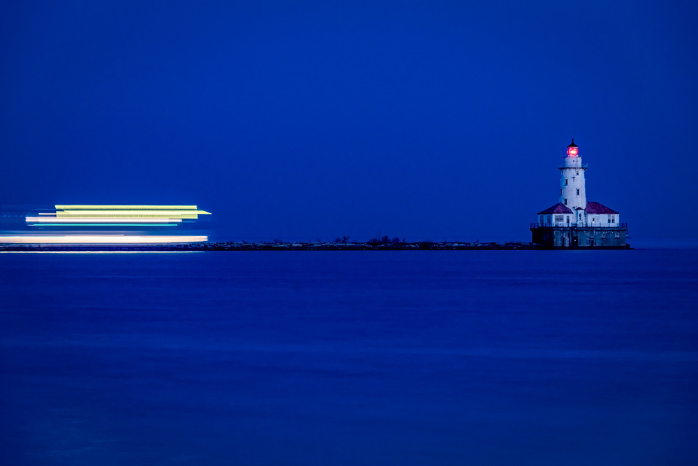 Passing ship near a lighthouse on Lake Michigan at blue hour