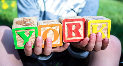 [Image description: An image of a child's hands holding blocks. The blocks spell out york.]