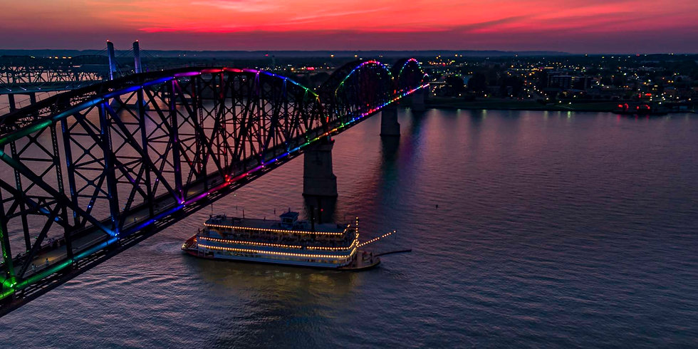 [Image description: A photograph of the Ohio River at dusk. Sailing on the river is a steamboat, going under a silhouetted bridge covered in rainbow colored lights.]