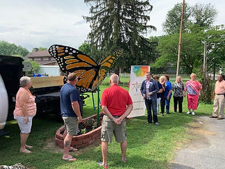 [Image description: An image of people gathered around a large butterfly sculpture for the Utica dedication.]