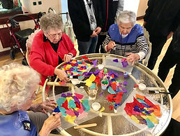 [Image description: An image of seniors gathered around a table, working with colorful tissue paper.]