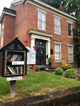 [Image description: An image of the front of the AASI building. In the foreground is a little library.]