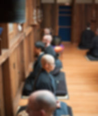 five people in black robes meditating in Zendo