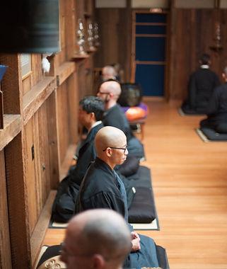 five people in black robes meditating in Zendo