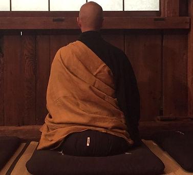 man in robes in seated meditation zazen