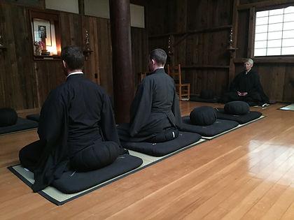 three people in black robes meditating in Zendo