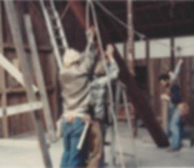 old photograph of four people lifting pillar to convert barn into Sonoma Mountain Zen Center zendo