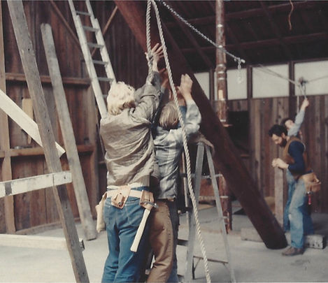 old photograph of four people lifting pillar to convert barn into Sonoma Mountain Zen Center zendo