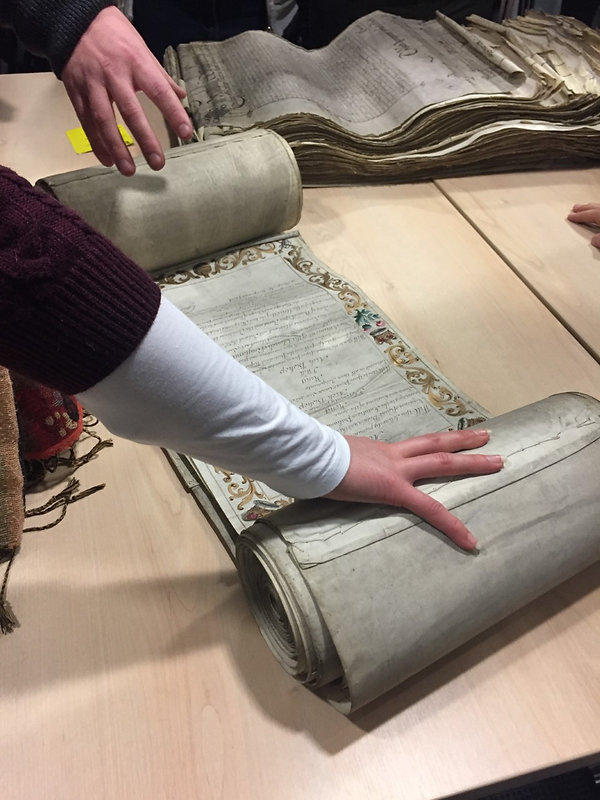 Students handling the coronation roll of George II (Catalogue reference: TNA, C 57/10)