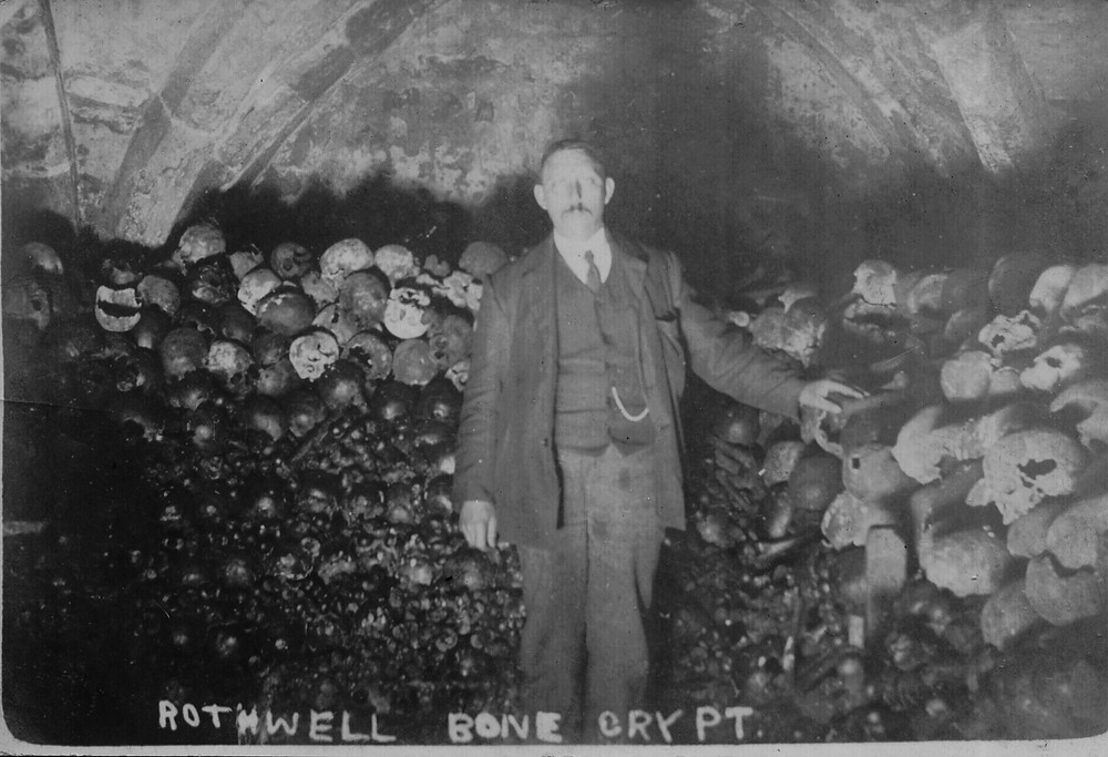 An Edwardian gentleman poses with the bones at Rothwell, c.1905. Rows of skulls punctuate the front of the bone stack,