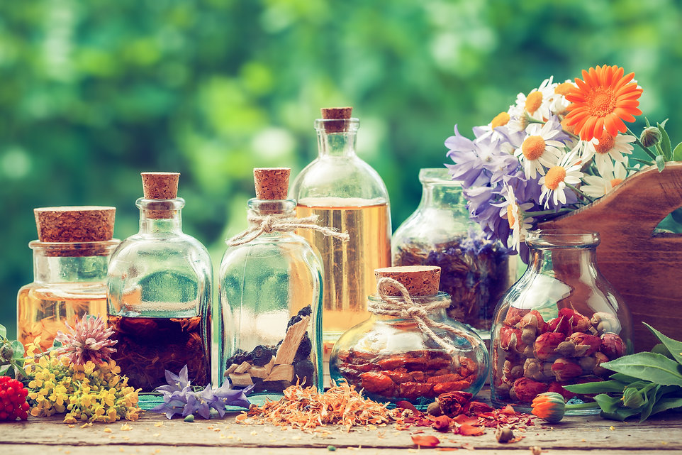 Bottles of tincture or potion and dry healthy herbs, bunch of healing herbs in wooden box