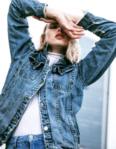 Woman in a jeans jacket with her arms covering her face