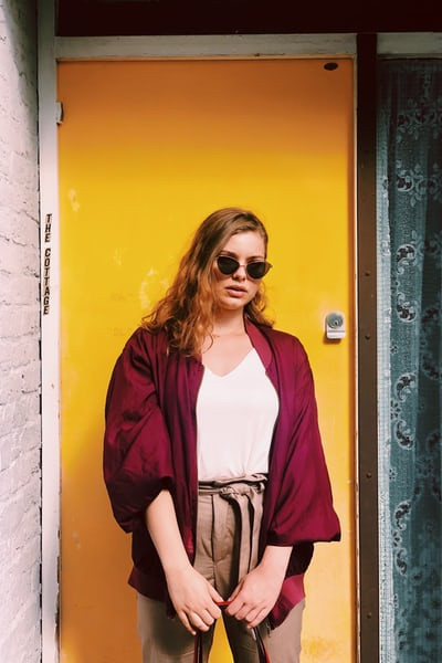 Woman standing wearinf a burgandy jacket with and wearing sunglasses