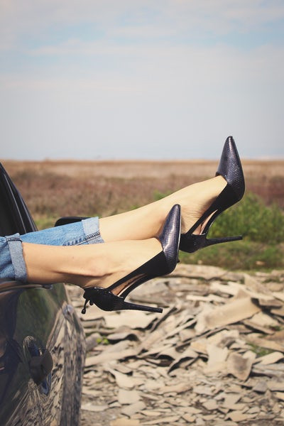A woman's feet with black pumps on it sticking out of car window