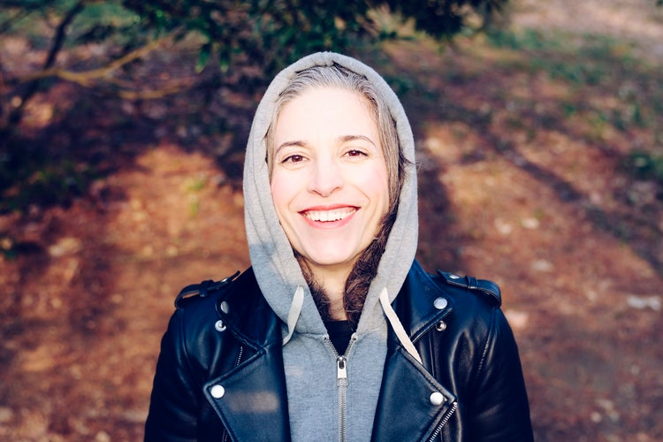 Smiling woman wearing a hoodie with a leather black jacket on top