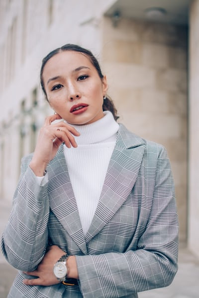 Woman with her hand by her face wearing a plaid blazer