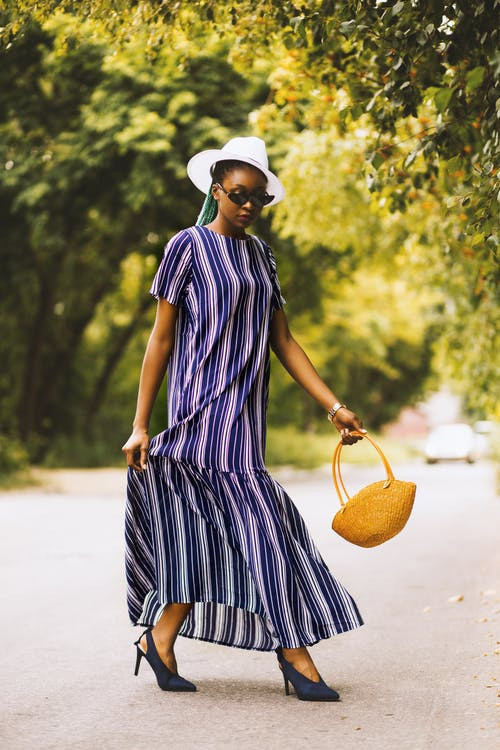 Woman in stripe dress walking with a basket bag in her hand