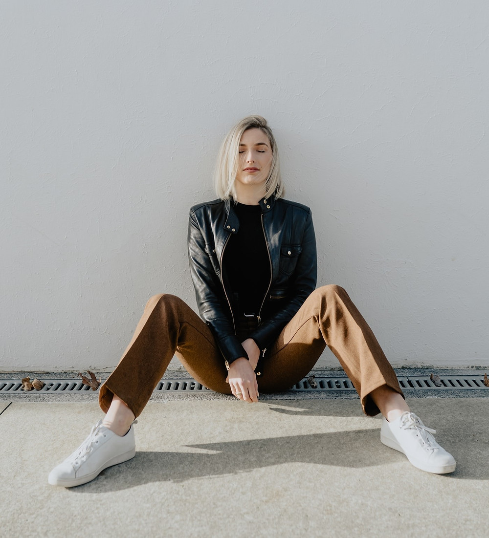 Woman sitting down on the ground with her eyes clothes