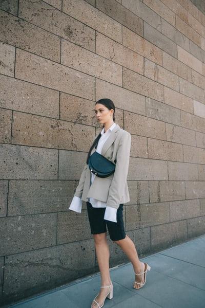 Woman wearing a blazer and shorts walking