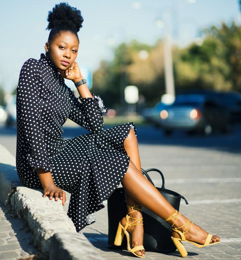 Woman sitting on sidewalk in a polka dot dress