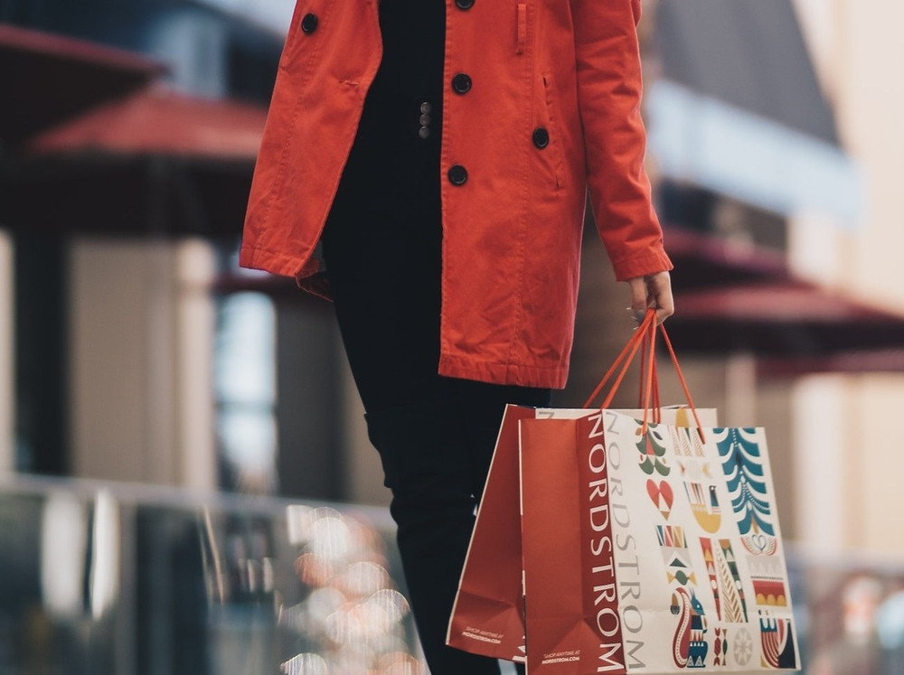 Woman in a red trench coat holding a Nordstrom shopping bag