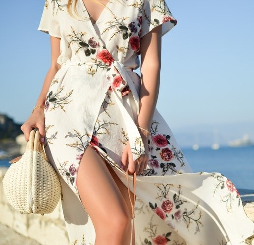 Woman walking on the beach in a floral wrap dress