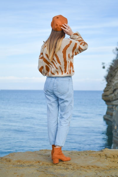 Woman wearing a sweater and light wash jeans looking into the sea