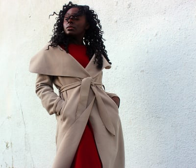woman standing with beige trench coat with hands in her pocket