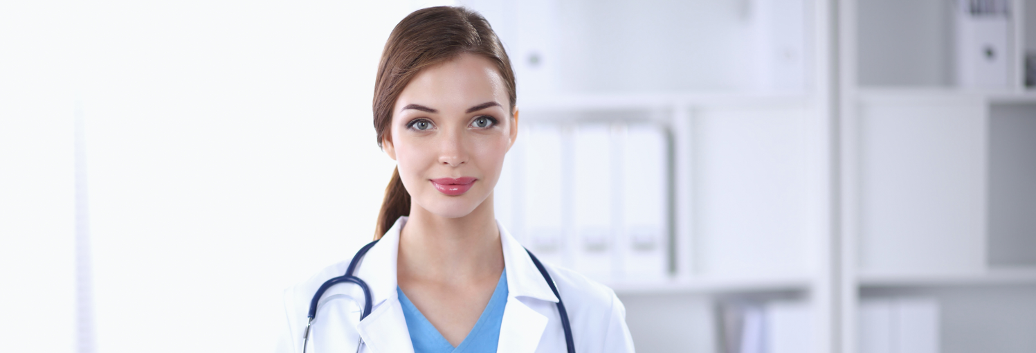 Portrait of young woman doctor with white coat standing in hosp_edited
