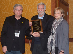 Dave and Jane Schumann receive a plaque appreciation for their funding of their Schumann-SCP Doctora