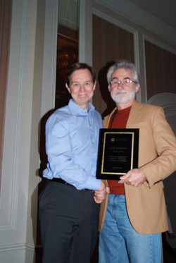 Eric Johnson receives the Scientific Achievement Award from Wes Hutchinson
