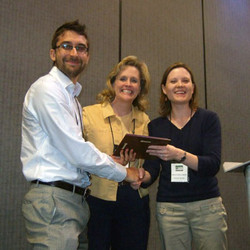 Maria Cronley and Peggy Sue Loroz presented Brent McFerran the Dissertation Competition Award