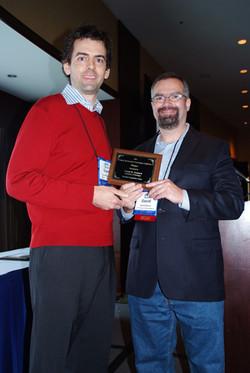 Grant Packard receives the Best Conferen