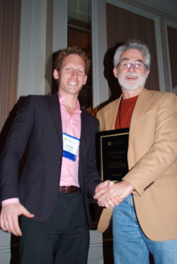 Jonah Burger receives the Early Career Award from Wes Hutchinson, Scientific Affairs Committee Chair