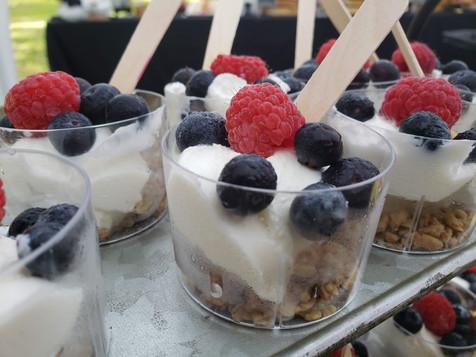 Single serve cups of yogurt parfaits on a buffet table.
