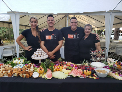 Chef Mike and 3 team memebers pose in front of a decorated grazing table.