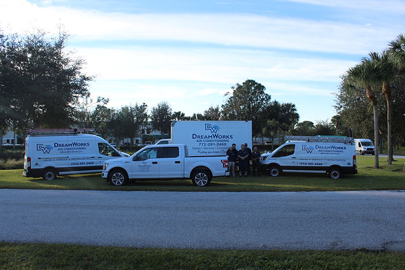 The DreamWorks Air Conditioning team poses with their company vehicles.