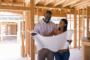 Young couple looking at blueprints in pa