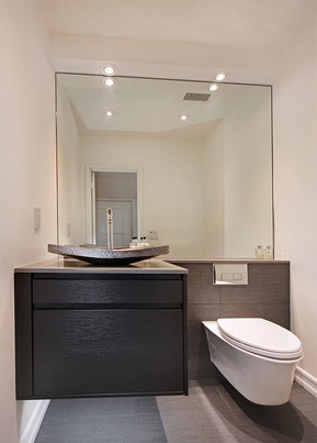 The powder room features a floating toilet and vanity with illumination underneath. A mirror and backsplash maximizes the small space.