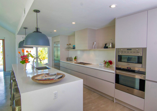 A long, sleek look is achieved with an extended waterfall island which creates a horizontal feel that compliments the handle-less cabinets on the cooktop area.