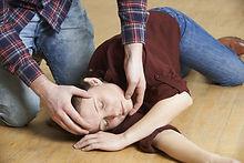 Homme formant à la position latérale de sécurité sur un enfant lors d'une formation GQS