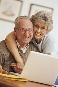 older couple embrassing in front of a computer and smiling