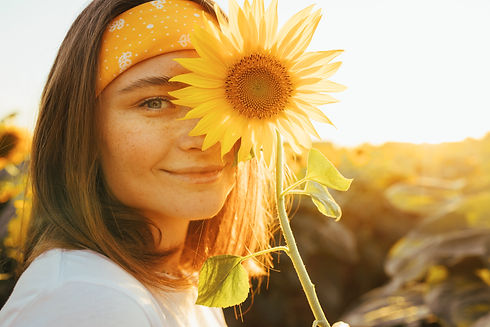 Lovely cheerful young woman posing alone on camera. Cover part of face with yellow sunflow