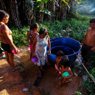 """Já na área urbana de São Gabriel da Cachoeira, às margens da BR-307, fica localizado o Barracão Yanomami. Crianças, adultos e idosos se aglomeram em redes dentro de duas estruturas muito precárias que servem como abrigo provisório para as famílias que chegam em busca de auxílio emergencial. Até a implementação de melhorias feitas pelo MSF, uma única fonte de água era utilizada para banhos e limpeza em geral.  Vilmar da Silva Matos é um líder indígena Yanomami que viaja de tempos em tempos de sua comunidade, Maturacá, para a cidade de São Gabriel da Cachoeira. Ele fala sobre o medo que sentiu quando soube pelo noticiário que a doença estava chegando cada vez mais perto do seu povo e atingia de forma mais dura os idosos. """"Nós pensávamos que estávamos perdidos, estávamos especialmente preocupados com os mais velhos. Nós tínhamos medo de perder as nossas lideranças, que são como nossos dicionários, nossos contadores de histórias"""".  São Gabriel da Cachoeira, AM - Brasil."""