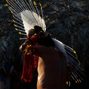 Karajá.  Ilha do Bananal - TO - Brasil.  A arte plumária é um aspecto marcante deste povo. Destaca-se o raheto, grande cocar feito de penas de urubu, coelheiro branco e rosa e de periquitos, usado pelos homens solteiros na ocasião das festas de iniciação dos meninos, conhecida como Casa Grande ou Hetohoky. Na cosmologia dos Karajás o sol era o raheto do urubu-rei que o herói mitológico (Kynyxiwe) feriu com uma flecha. Por isso, o sol anda devagar atravessando o céu durante o dia.  Texto: Museu Nacional / UFRJ.